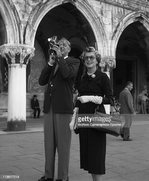 American actor Gary Cooper, shooting with a cinecamera, and his wife Veronica, wearing a black coat, white long gloves and holding a handbag, in...