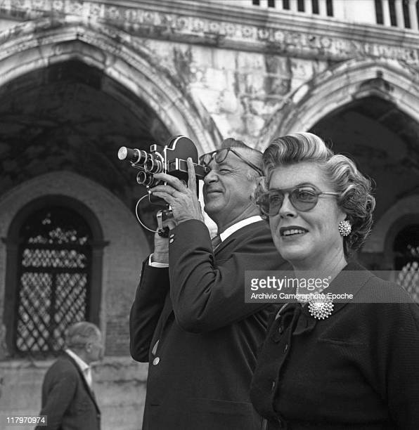 American actor Gary Cooper shooting with a cinecamera and his wife Veronica wearing a black coat a brooch earrings and sunglasses in StMark Square...