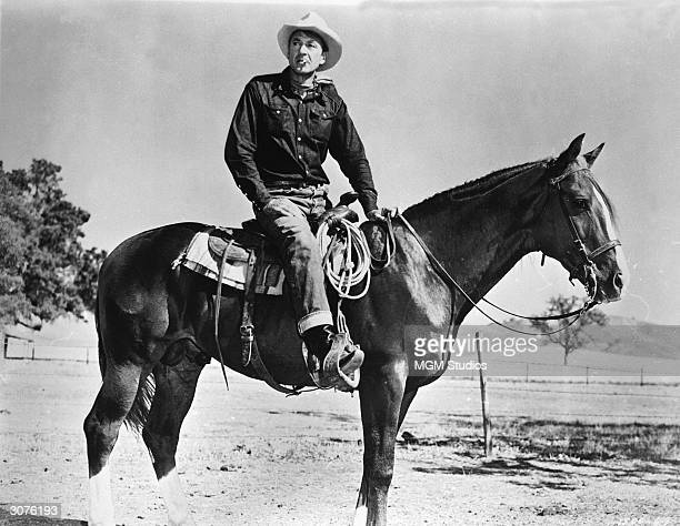 American actor Gary Cooper sits on his horse and smokes in a scene from the film, 'It's a Big Country,' which features segments directed by seven...