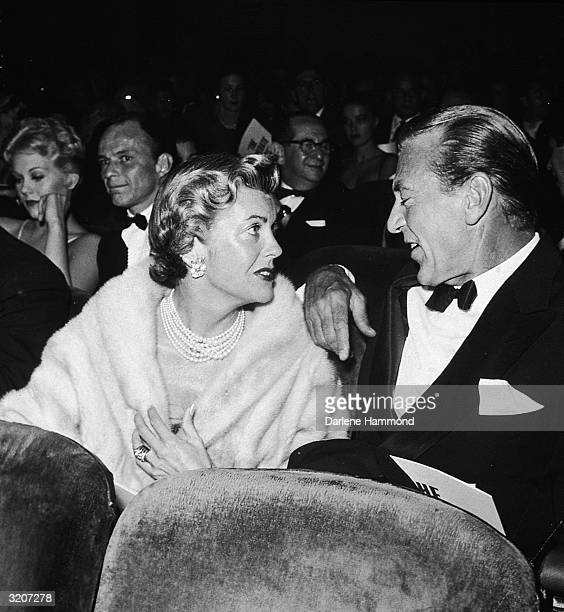 American actor Gary Cooper sitting in a theatre and talking to his wife Rocky also known as Veronica Cooper or actor Sandra Shaw at the premiere of...