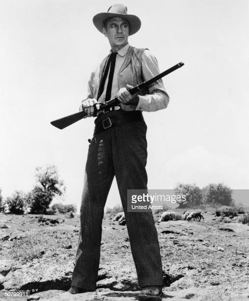 American actor Gary Cooper stands with a gun in a still from the film, 'Vera Cruz,' directed by Robert Aldrich, 1954.