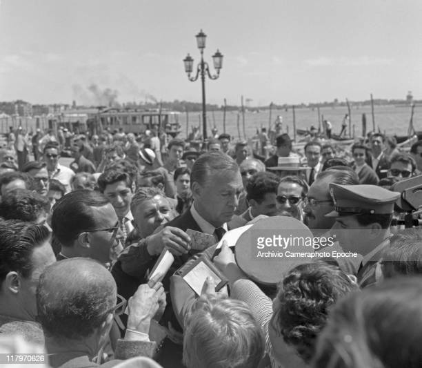 American actor Gary Cooper surrounded by the crowd asking for autographs in Riva degli Schiavoni St Marks Square Venice 1955