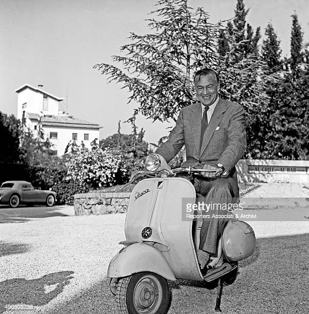American actor Gary Cooper visiting Rome having fun in posing on a Vespa Rome
