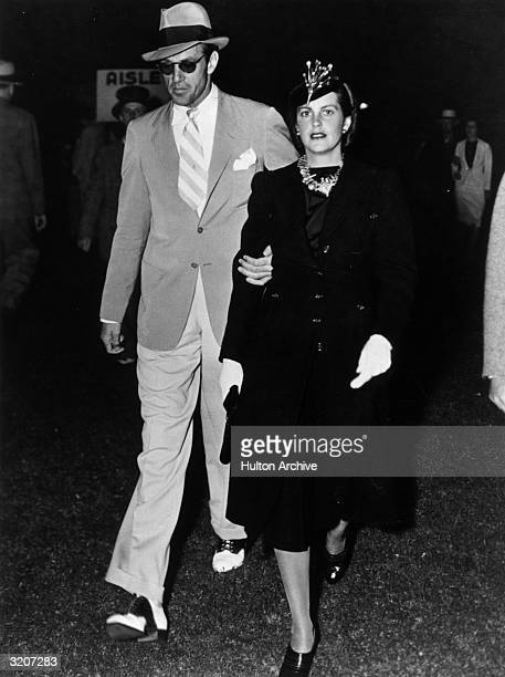 American actor Gary Cooper walking with his wife 'Rocky' actor Sandra Shaw He is wearing sunglasses and a hat and she is wearing a dark suit