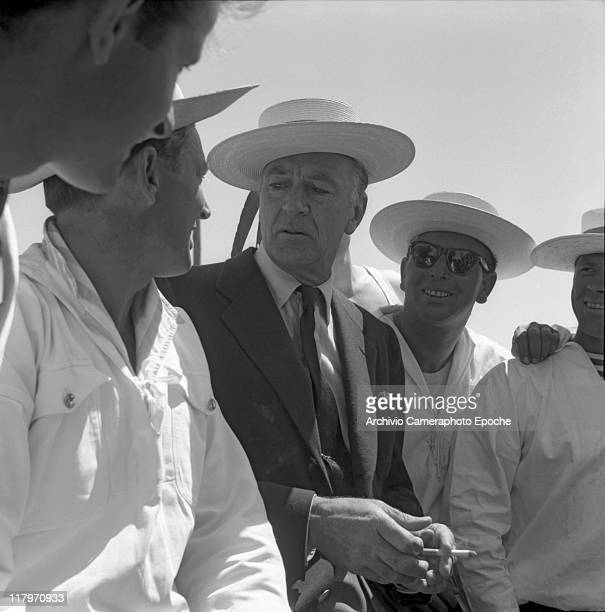 American actor Gary Cooper wearing a blazer a tie and a straw hat smoking a cigarette surrounded by gondoliers wearing straw hats and white shirts...