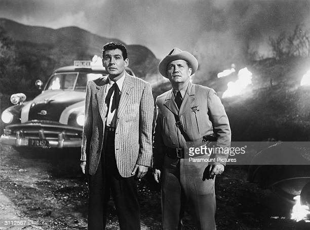 American actor Gene Barry and an unidentified man stand outdoors looking in the distance with amazement in a still from the film 'The War Of The...