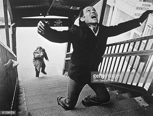 1971 American actor Gene Hackman as New York City detective Popeye Doyle shoots French actor Marcel Bozzuffi in the back on the stairs of an elevated...