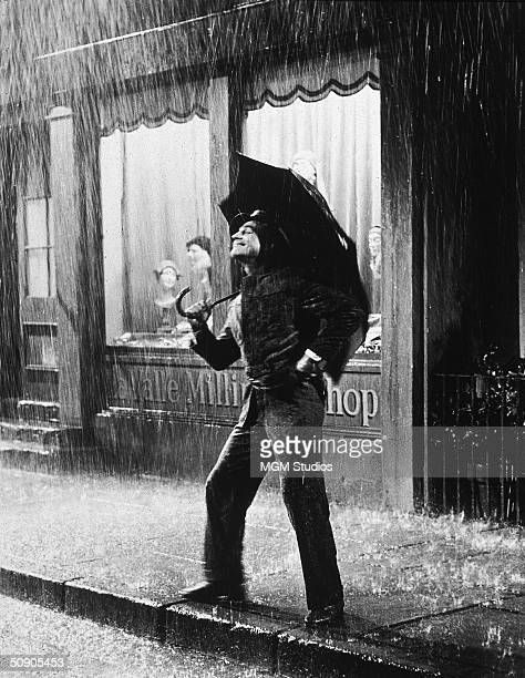 American actor Gene Kelly stands on a sidewalk smiling and holding an umbrella during a downpour in a still from the film 'Singin' in the Rain'...