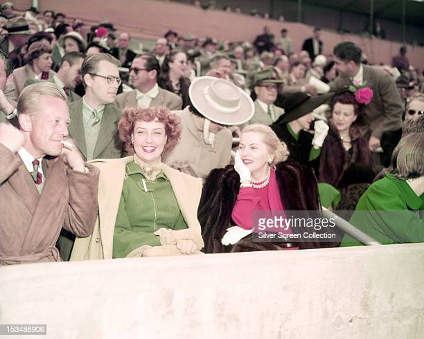 American actor Gene Raymond with his wife singer and actress Jeanette MacDonald in the crowd at an event circa 1950