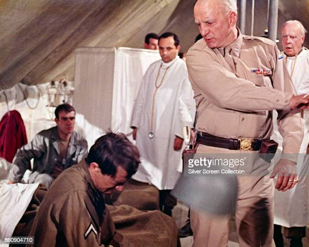 American actor George C Scott as he knocks a soldier's helmet off in a scene from 'Patton' 1970