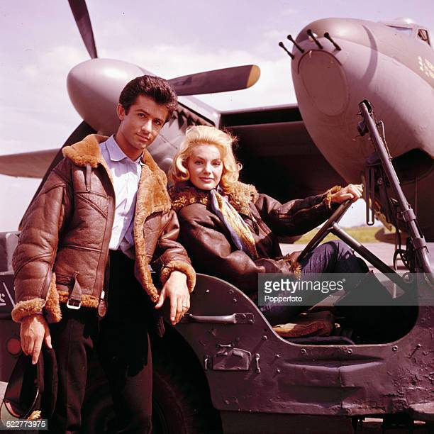 American actor George Chakiris and Austrian actress Maria Perschy posed together wearing sheepskin lined leather jackets in front of a de Havilland...