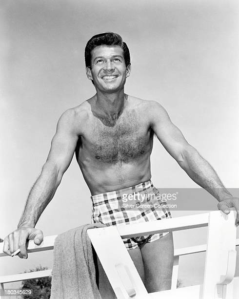 American actor George Nader wearing swimming trunks in a promotional portrait for 'Four Girls In Town' directed by Jack Sher 1957