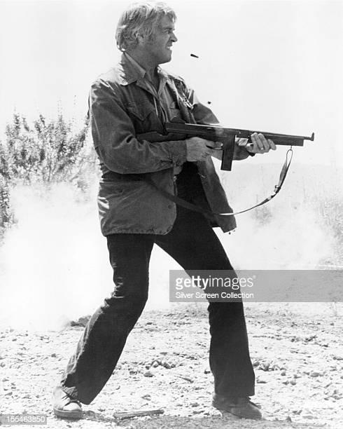 American actor George Peppard firing a machine gun as Vince Newman in 'Newman's Law' directed by Richard T Heffron 1974