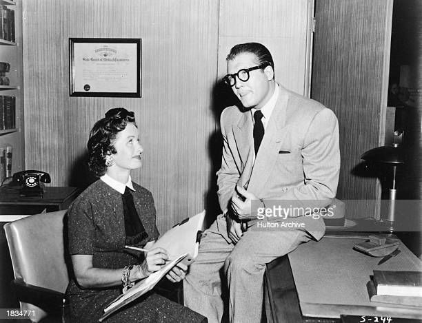 American actor George Reeves as Clark Kent sits on desk beside Noel Neill as Lois Lane in a still from the television series 'Adventures of Superman'...
