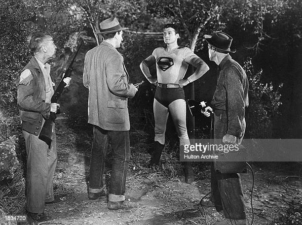 American actor George Reeves as Superman stands behind a group of armed men in a still from the television series 'Adventures of Superman' or a still...