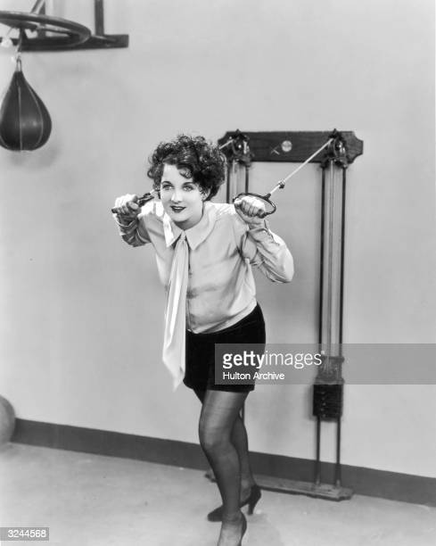 American actor Gertrude Olmstead pulls on the cables of an exercise machine in a still from director Jack Conway's silent film 'Bringing Up Father'...