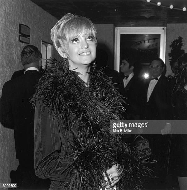 American actor Goldie Hawn poses in a grosgrain jacket trimmed with ostrich plumes at an annual Thalian Ball California