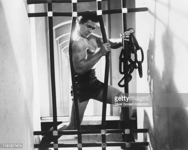 American actor Gordon Scott bending the bars of a cage as the hero of the Italian film 'Maciste contro il vampiro', aka 'Goliath and the Vampires',...