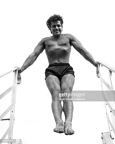 American actor Gordon Scott posing in swimming trunks, at the top of a flight of steps, circa 1960.