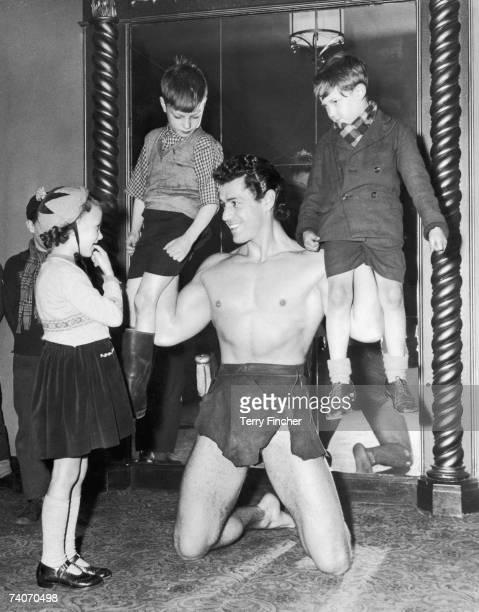 American actor Gordon Scott star of Tarzan's Hidden Jungle' visits the Granada Cinema in Clapham Junction and meets children attending a matinee of...