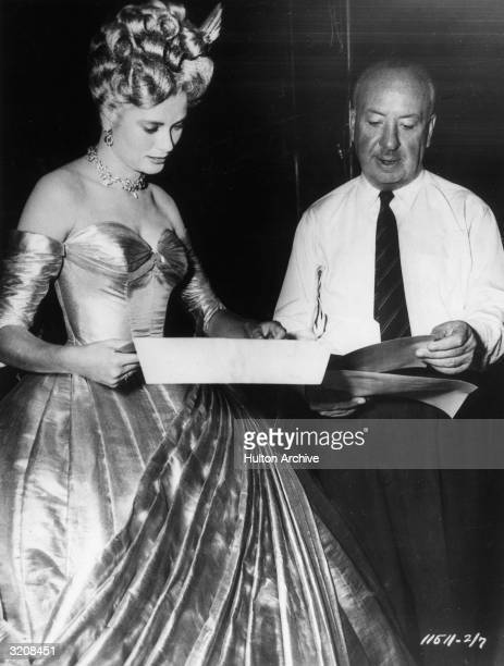 American actor Grace Kelly and British film director Alfred Hitchcock review a script on the set of the film 'To Catch a Thief' Kelly wears a...