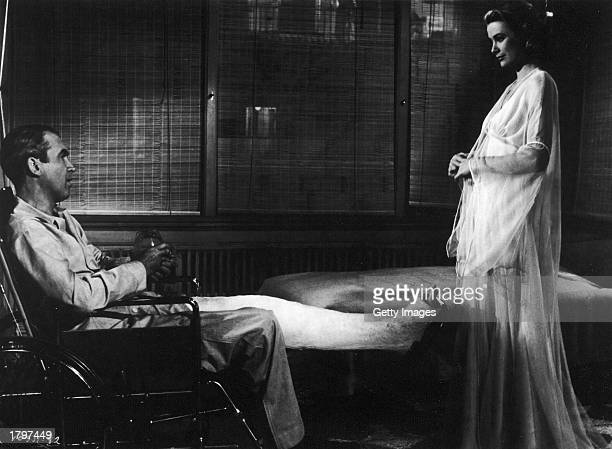 American actor Grace Kelly models a nightgown for actor James Stewart who sits in a wheelchair with his leg in cast in a still from director Alfred...