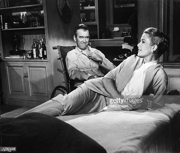American actor Grace Kelly reclines on a bed while actor James Stewart smiles at her from a wheelchair in a still from director Alfred Hitchcock's...