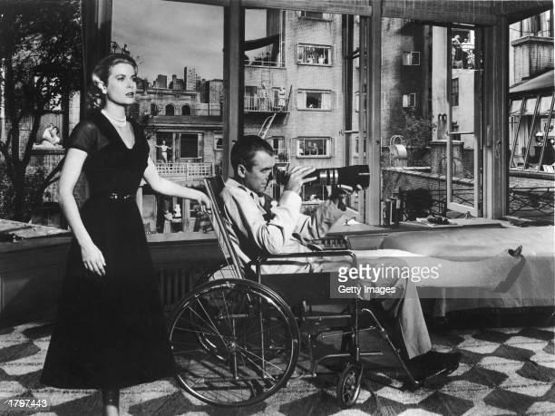 American actor Grace Kelly stands behind actor James Stewart who sits in a wheelchair with his leg in cast while he uses the telephoto lens of his...