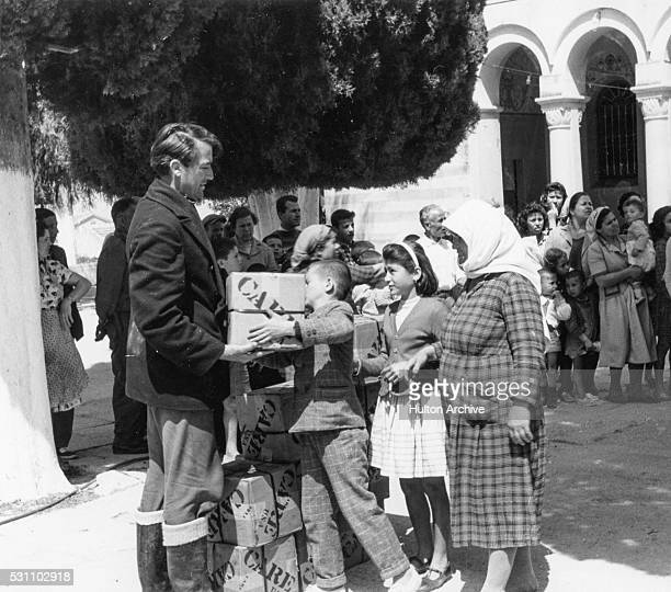 American actor Gregory Peck delivers CARE packages to families, Greece, 1940s or 1950s. CARE was a humanitarian agency, its acronym later changed to...