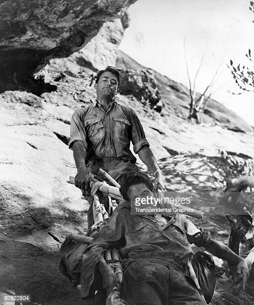 American actor Gregory Peck pulls British actor Lyndon Brook up a hill on a makeshift stretcher in a scene from 'The Purple Plain' Caeylon 1954