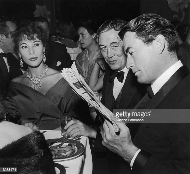American actor Gregory Peck reads a newspaper review of director John Huston's film, 'Moby Dick' while his wife, Veronique, and Huston himself look...