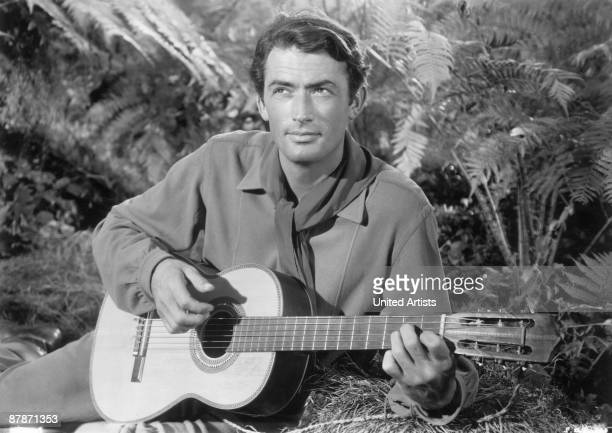 American actor Gregory Peck strums a guitar in a still from director King Vidor's film 'Duel in the Sun' 1946