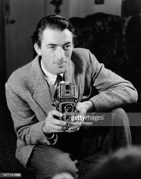 American actor Gregory Peck using a Rolleiflex camera at his home in Gloucester Square, London, 1950. He is working on the film 'Captain Horatio...