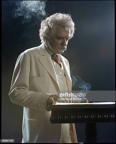 American actor Hal Holbrook as Samuel L Clemens stands at a podium with a smoking cigar in a scene from the television production of the oneman play...