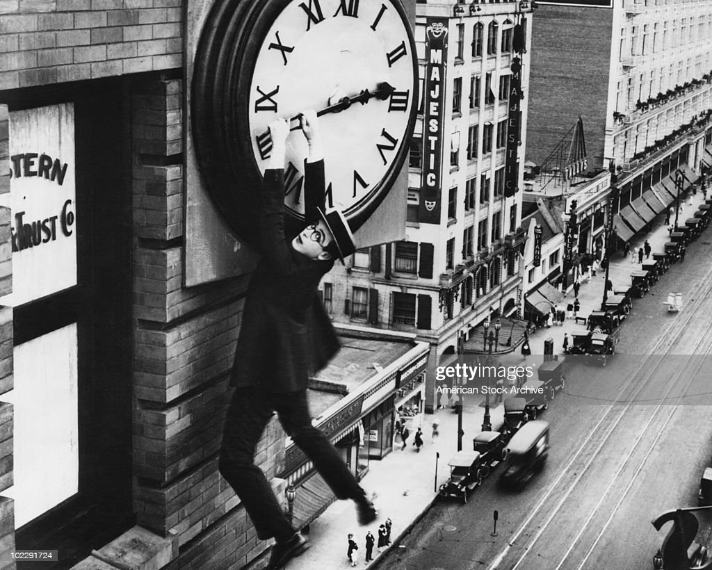 American actor Harold Lloyd (1893 - 1971) finds himself in a precarious situation dangling from a clock in a scene from the film 'Safety Last!', 1923.