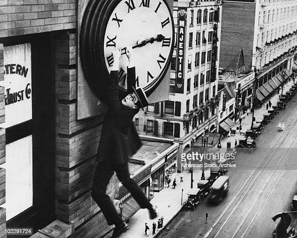 American actor Harold Lloyd finds himself in a precarious situation dangling from a clock in a scene from the film 'Safety Last' 1923