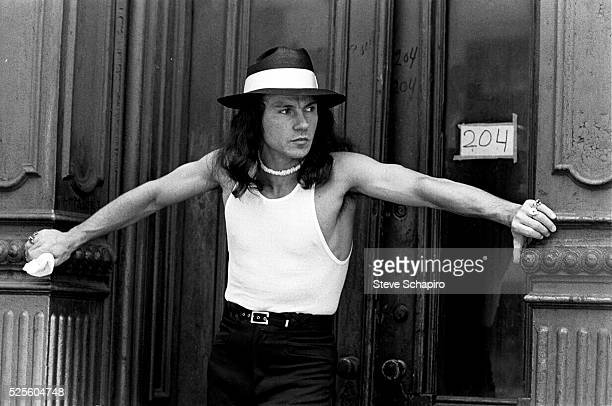American actor Harvey Keitel, stands wearing a white vest, a trilby and a necklace, with his hands on either side of the door, as his character...
