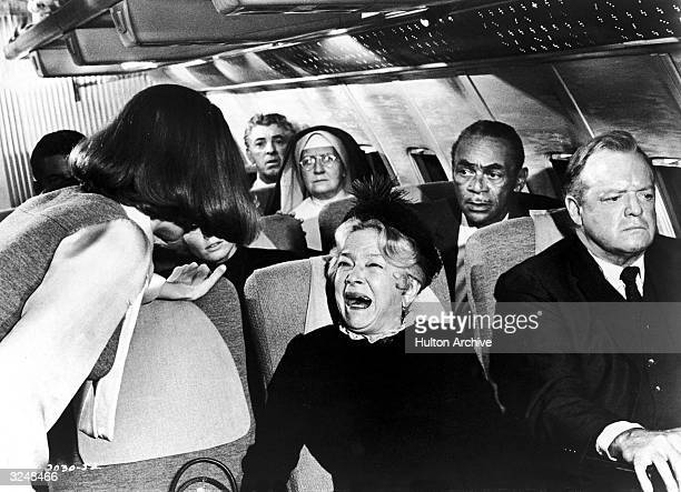 American actor Helen Hayes cries hysterically as a flight attendant attempts to calm her and American actor Van Heflin looks away in a still from the...