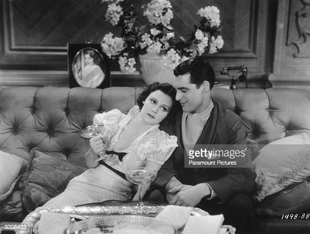 American actor Helen Mack and Britishborn actor Cary Grant lounge on a sofa and drink champagne in a still from the film 'Kiss and Make Up' directed...