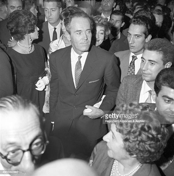 American actor Henry Fonda standing surrounded by many people in the hall of the Sistina Theatre where he will attend Harry Belafonte's concert Rome...