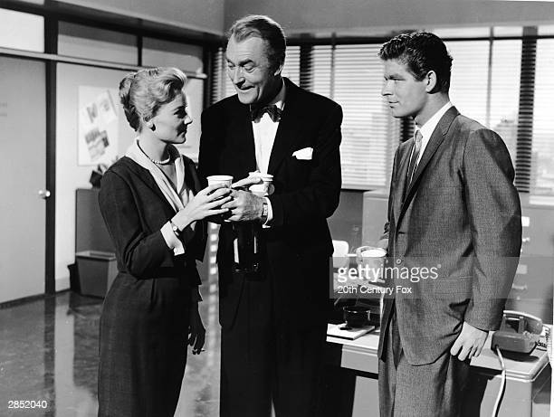 American actor Hope Lange takes a paper cup from British actor Brian Aherne who also holds a bottle while Irish actor Stephen Boyd stands nearby in a...