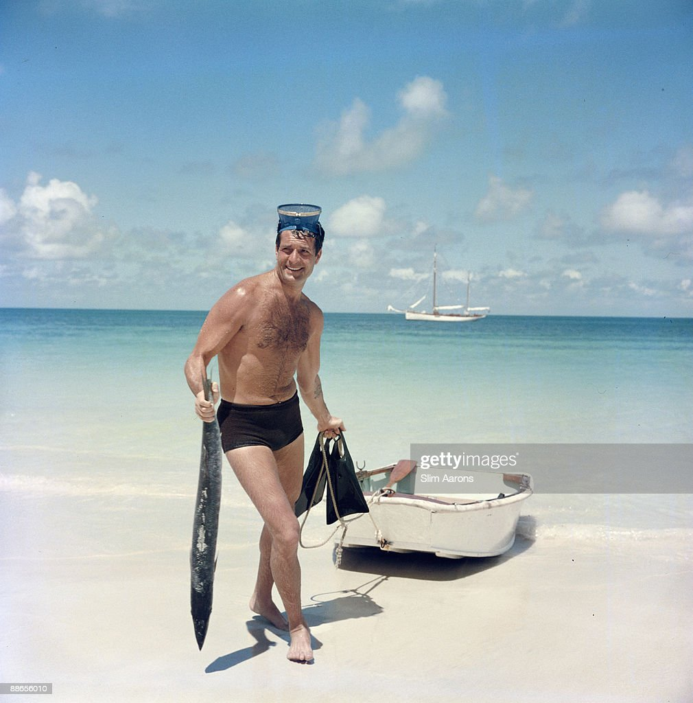 American actor Hugh O'Brian returns to the beach with a fish after a snorkelling expedition, Antigua in the West Indies, 1961.