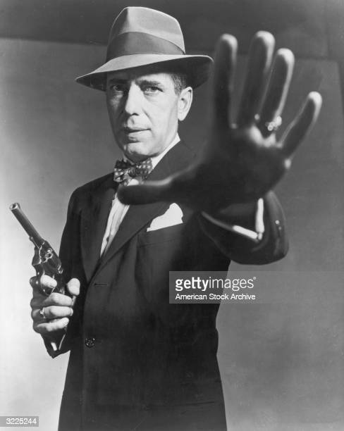 American actor Humphrey Bogart carrying a gun and holding out his hand in a still from director Bretaigne Windust's film 'The Enforcer'