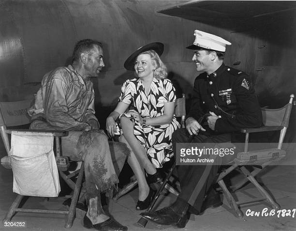 American actor Humphrey Bogart chats with his wife actor Mayo Methot and Dutchborn actor Philip Dorn while sitting in front of an airplane on the set...
