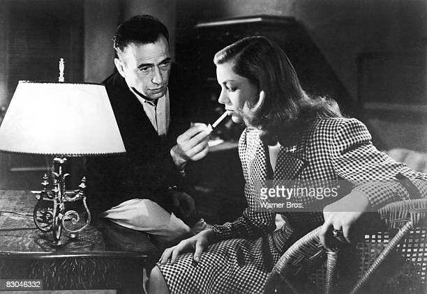 American actor Humphrey Bogart lights a cigarette for actress Lauren Bacall in a still from the film 'To Have and Have Not' directed by Howard Hawks...