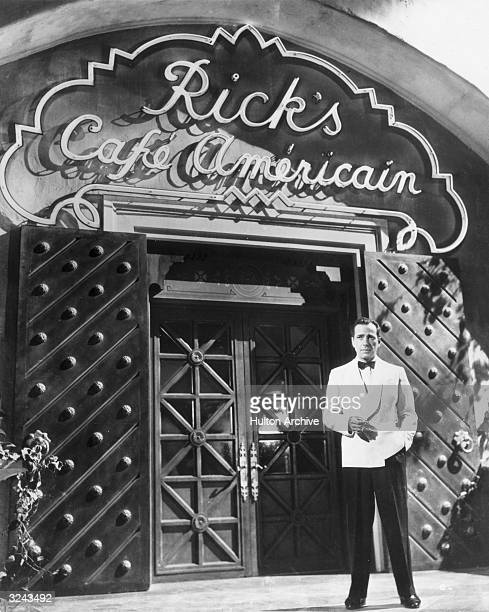 American actor Humphrey Bogart smokes a cigarette outside Rick's Cafe Americain in a publicity still from director Michael Curtiz's film 'Casablanca'