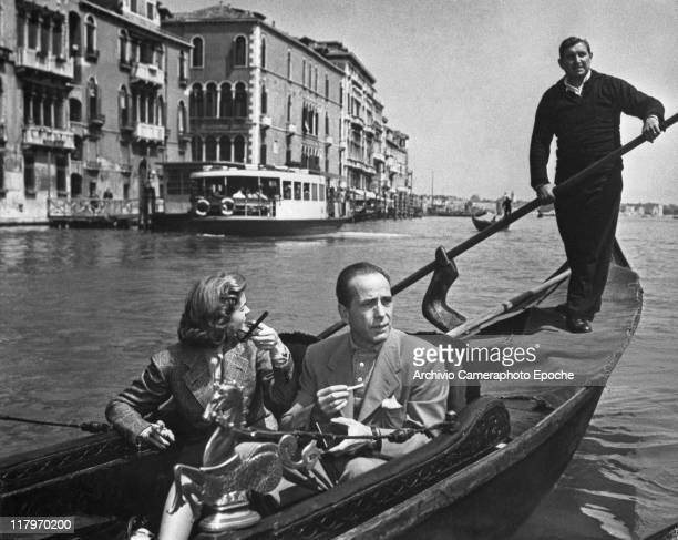 American actor Humphrey Bogart smoking a cigarette with his wife Lauren Bacall sitting on a gondola the gondolier behind them rowing in Stmark's...