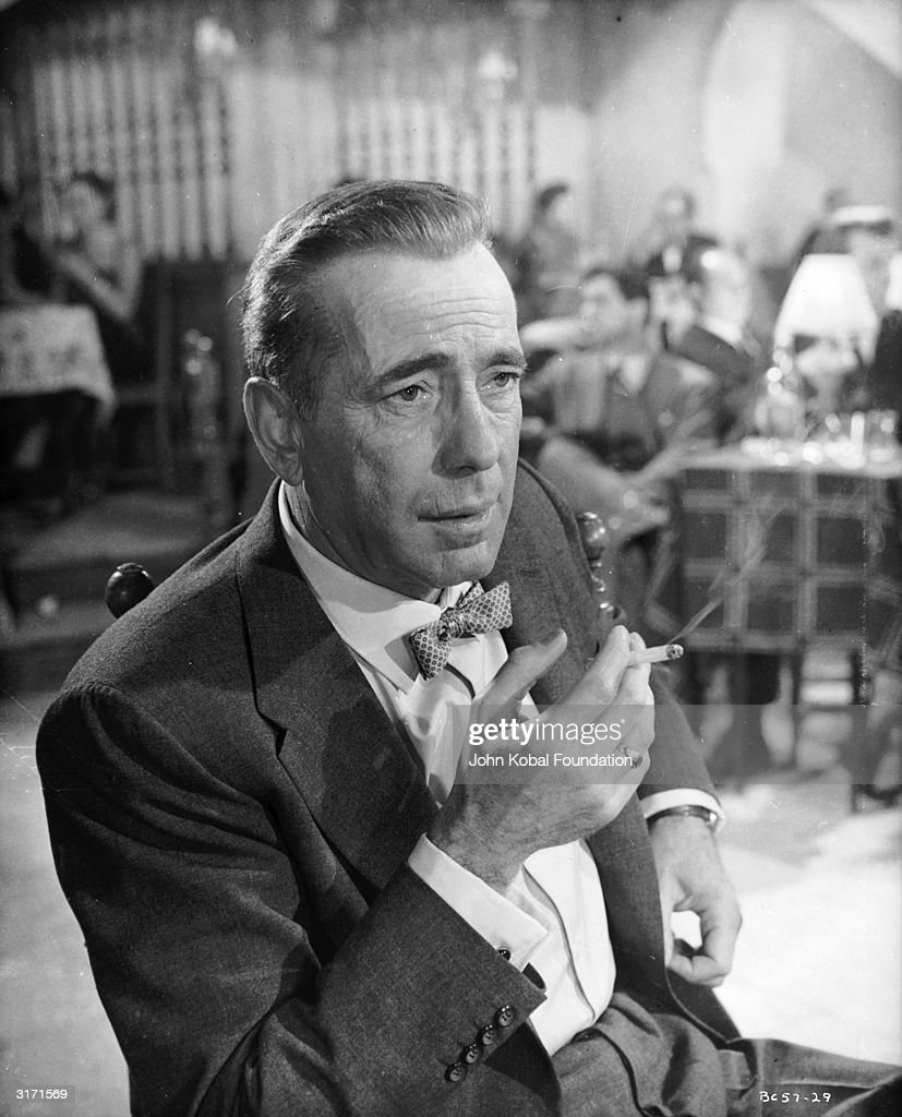 American actor Humphrey Bogart (1899 - 1957) smoking in a cafe in a scene from 'The Barefoot Contessa'.