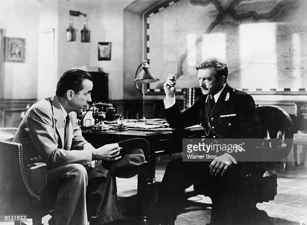 American actor Humphrey Bogart talks to British actor Claude Rains at a cafe table in a still from the film 'Casablanca' directed by Michael Curtiz...