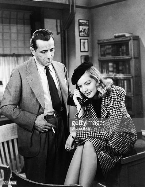 American actor Humphrey Bogart watches actor Lauren Bacall as she sits on top of his desk and talks on the telephone in a still from director Howard...